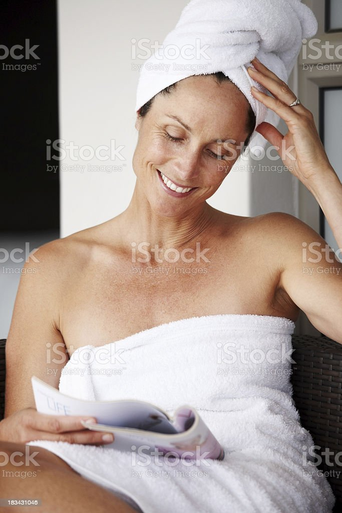Mature woman in towel reading magazine royalty-free stock photo