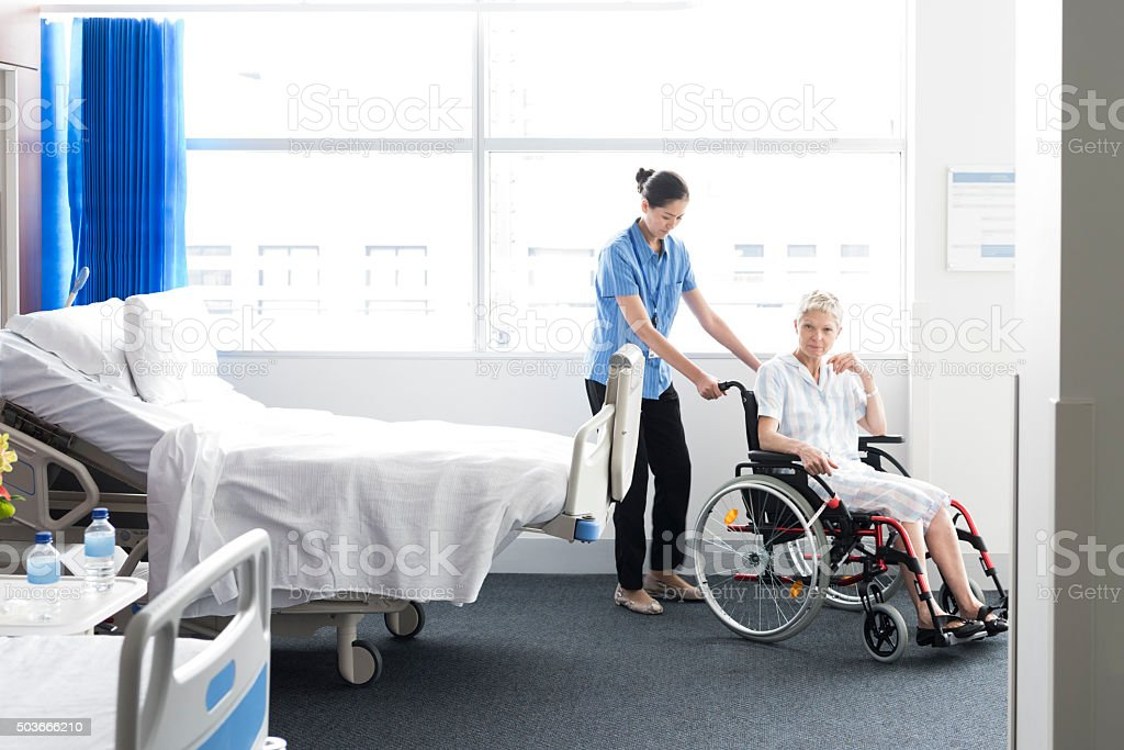 Mature woman in wheelchair with nurse in hospital room stock photo