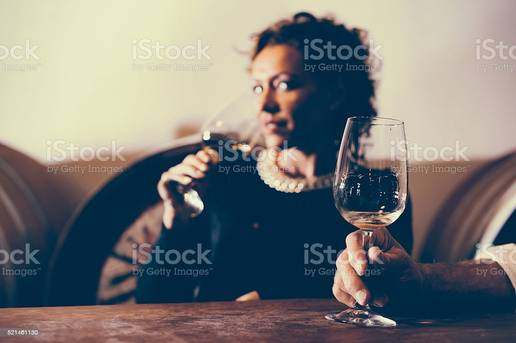 Mature Woman in Winery Cellar with Glass of White Wine stock photo