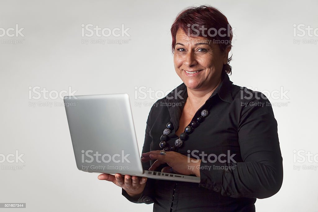 Mature woman isolated on gray background holding a laptop stock photo