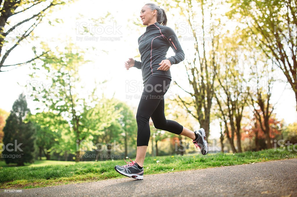 Mature Woman Jogging Outdoors stock photo