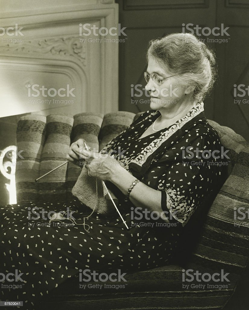 Mature woman knitting in living room, (B&W) stock photo