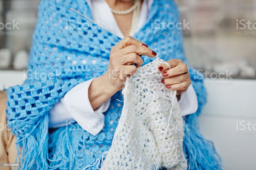 Mature woman knitting stock photo