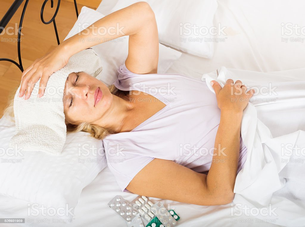 Mature woman laying in bed with towel stock photo