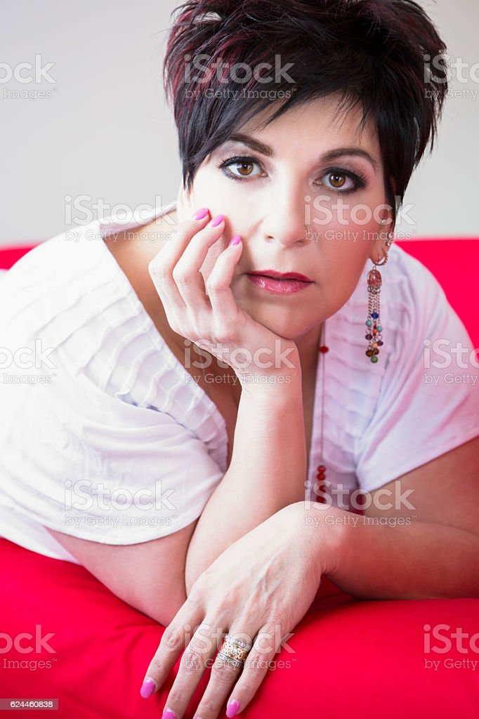 Mature woman laying on couch stock photo