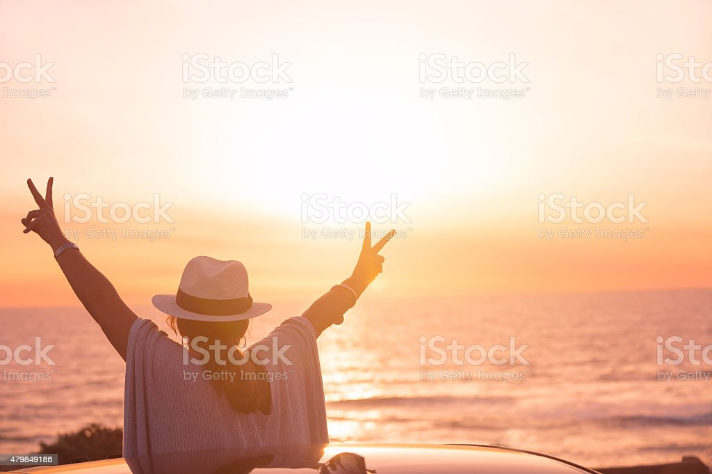Mature woman leaning out of sunroof at sunset. stock photo