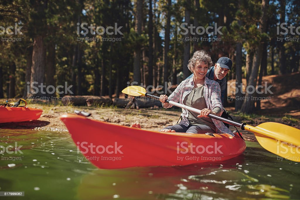 Mature woman learning to row in kayak stock photo