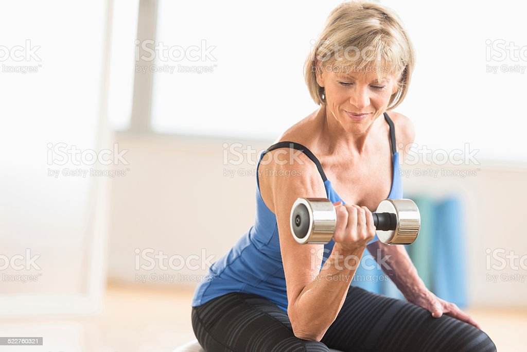 Mature Woman Lifting Dumbbell At Home stock photo