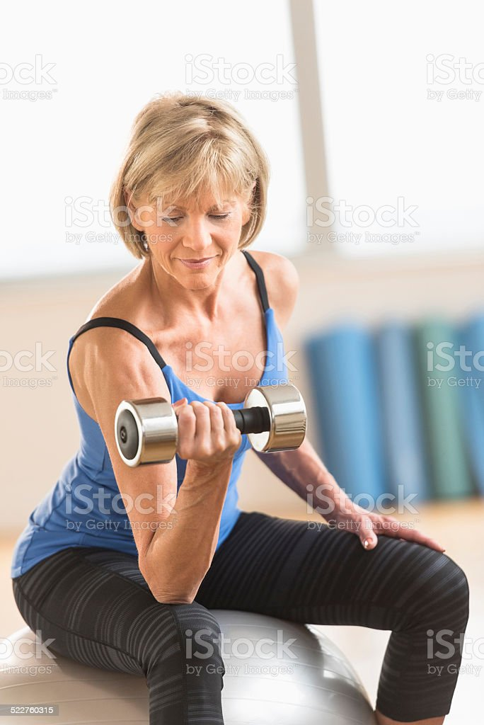 Mature Woman Lifting Dumbbell On Fitness Ball stock photo