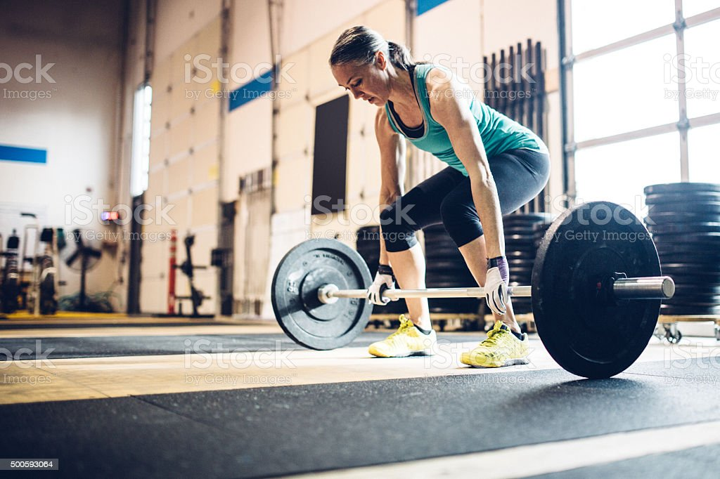 Mature Woman Lifting Weights in Gym Setting stock photo