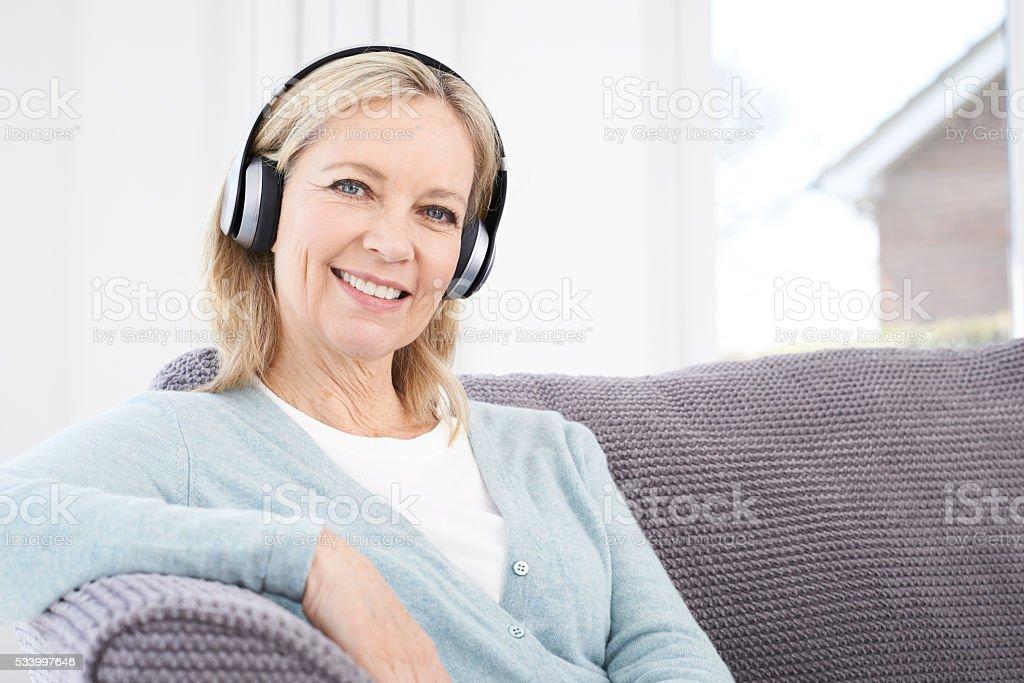 Mature Woman Listening To Music On Wireless Headphones stock photo