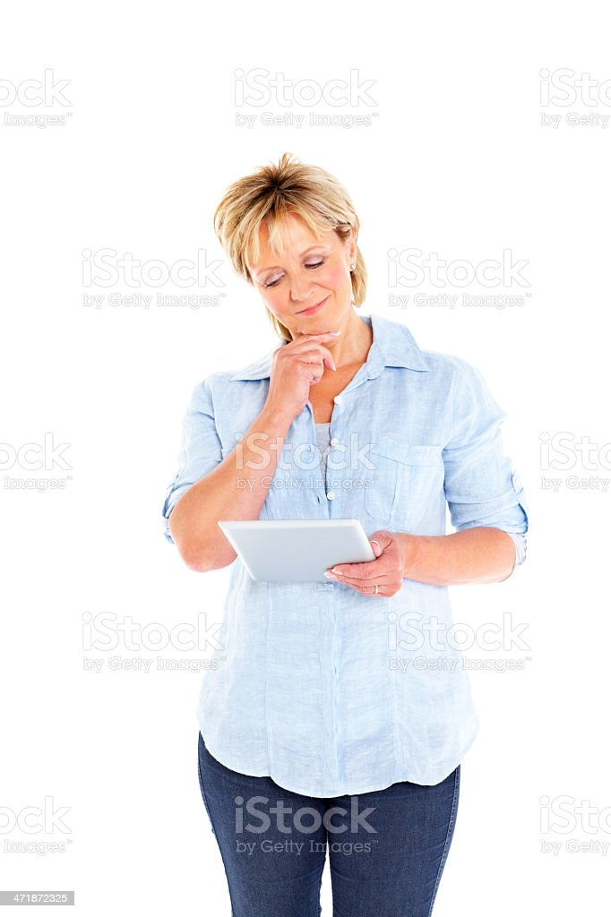 Mature woman looking at digital tablet and thinking royalty-free stock photo