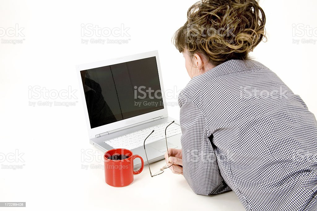 Mature woman looking at laptop with cup of coffee royalty-free stock photo