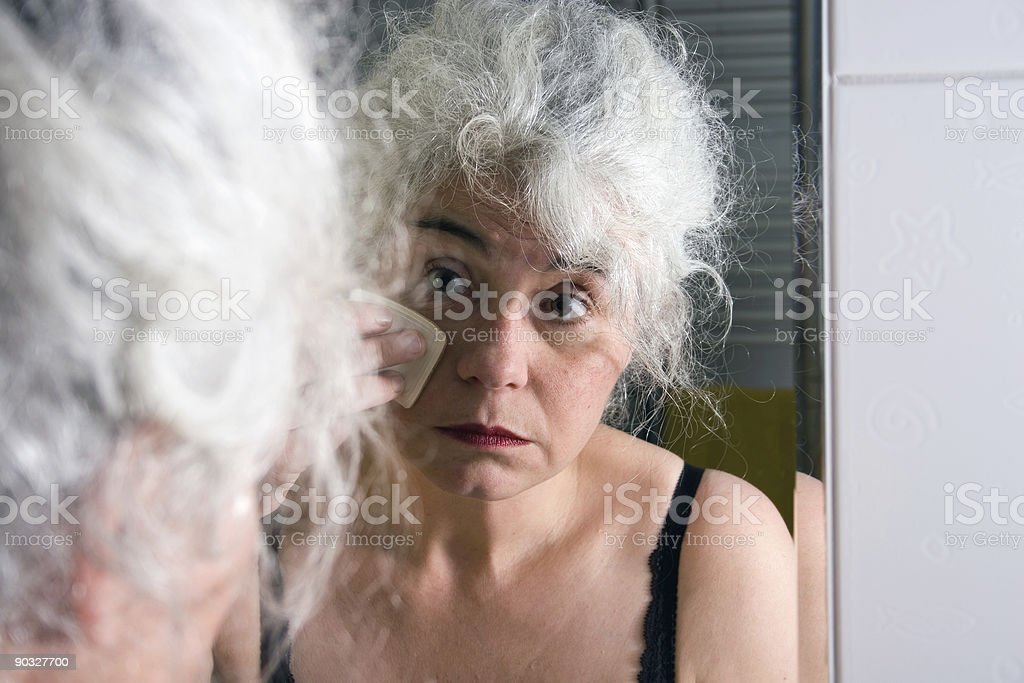 Mature Woman looking in the mirrow royalty-free stock photo