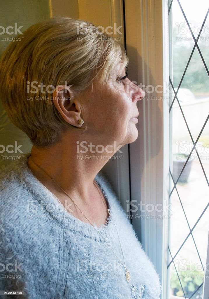 Mature woman looking out of a window stock photo