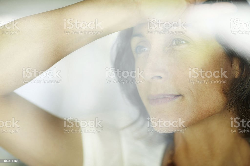 Mature woman looking through a glass window royalty-free stock photo