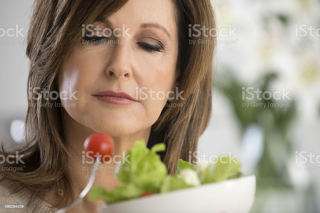 Mature woman looking unhappy about food stock photo