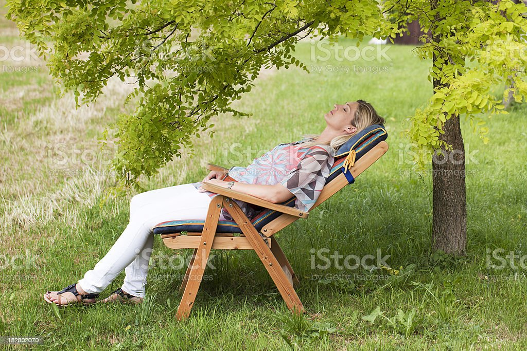 Mature woman lying relaxed on deck chair under tree (XXL) royalty-free stock photo