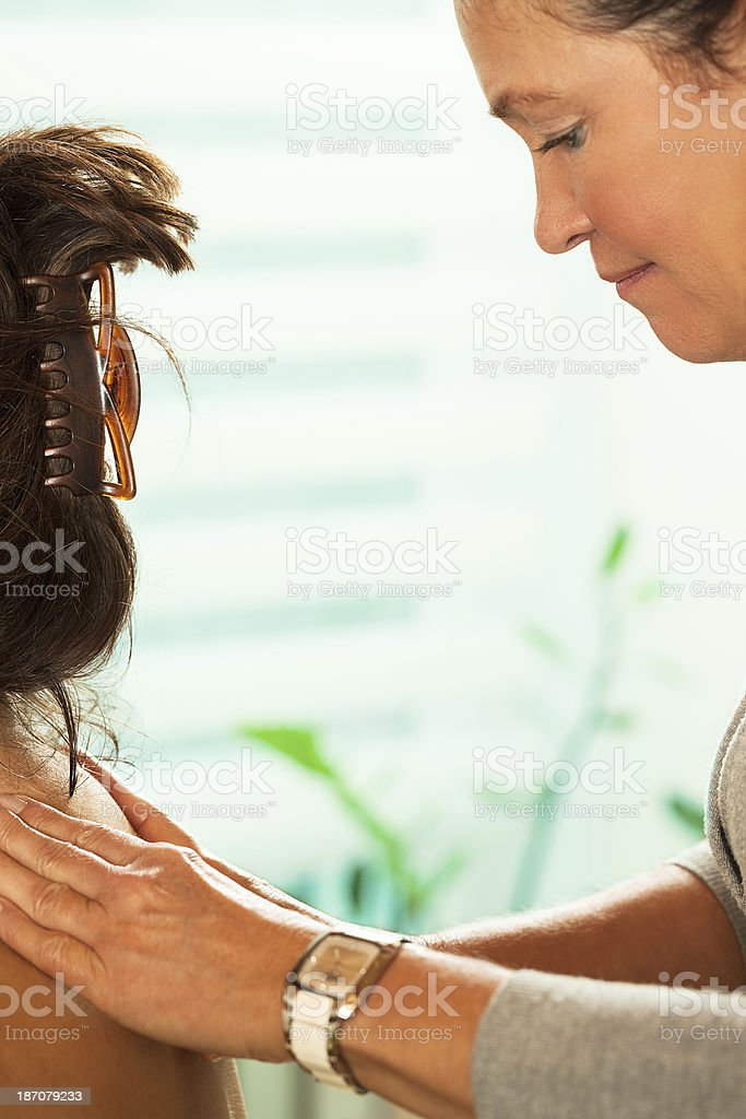 Mature woman massaging client's shoulders royalty-free stock photo