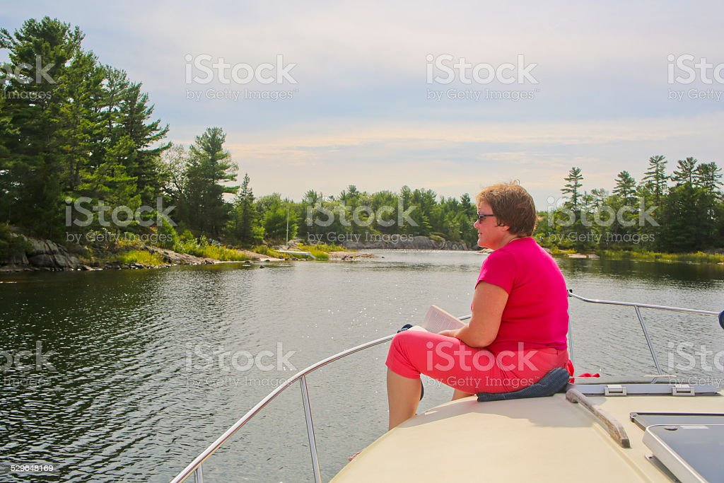 Mature Woman Meditating on a Yacht's Foredeck stock photo
