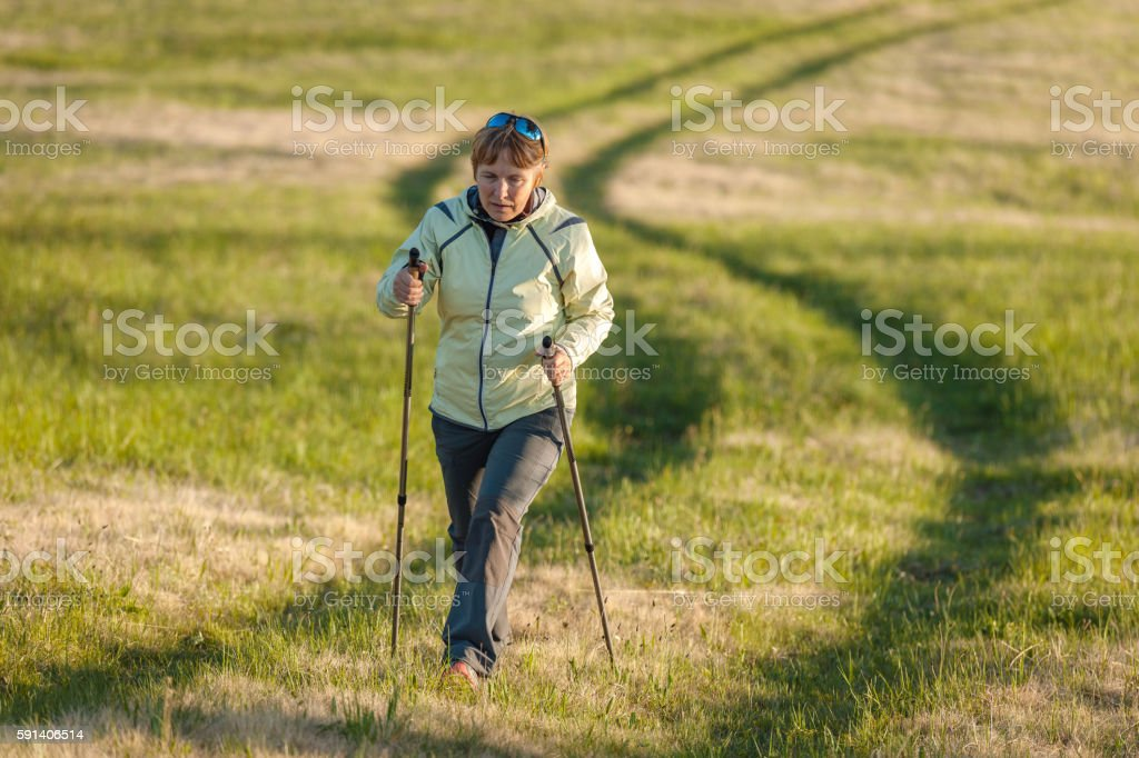 Mature Woman Nordic Walking on Plateau, Slovenia, Europe stock photo