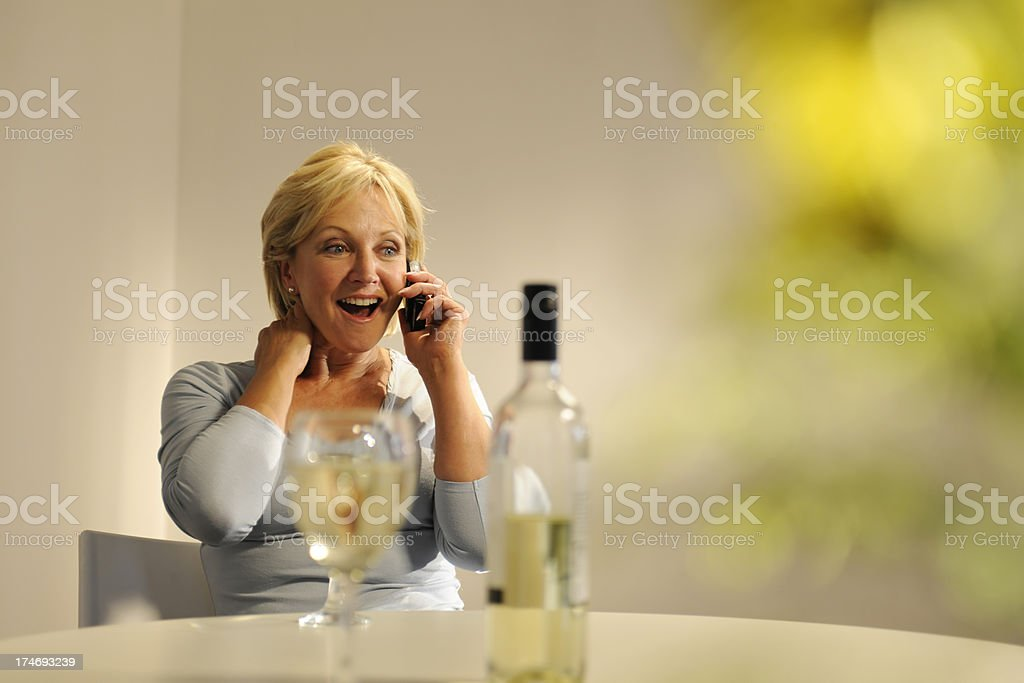 Mature Woman On Mobile Phone Drinking Wine royalty-free stock photo
