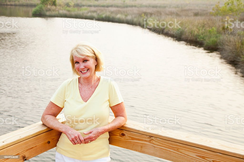 Mature woman on terrace by water stock photo