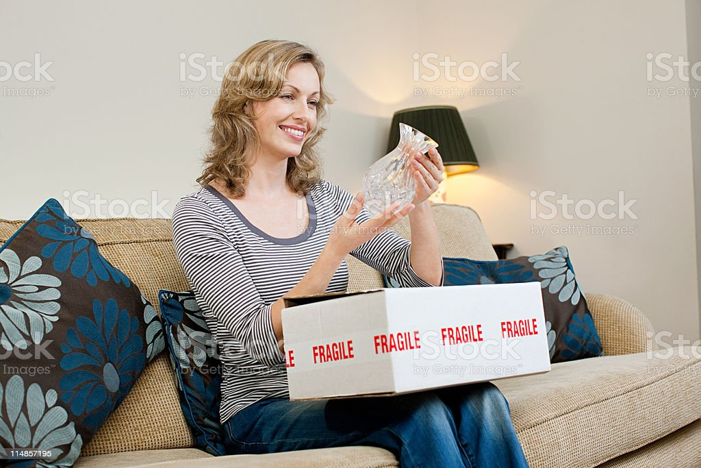Mature woman opening parcel containing glass vase stock photo