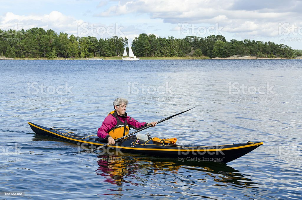 Mature woman paddling a black sea kayak stock photo