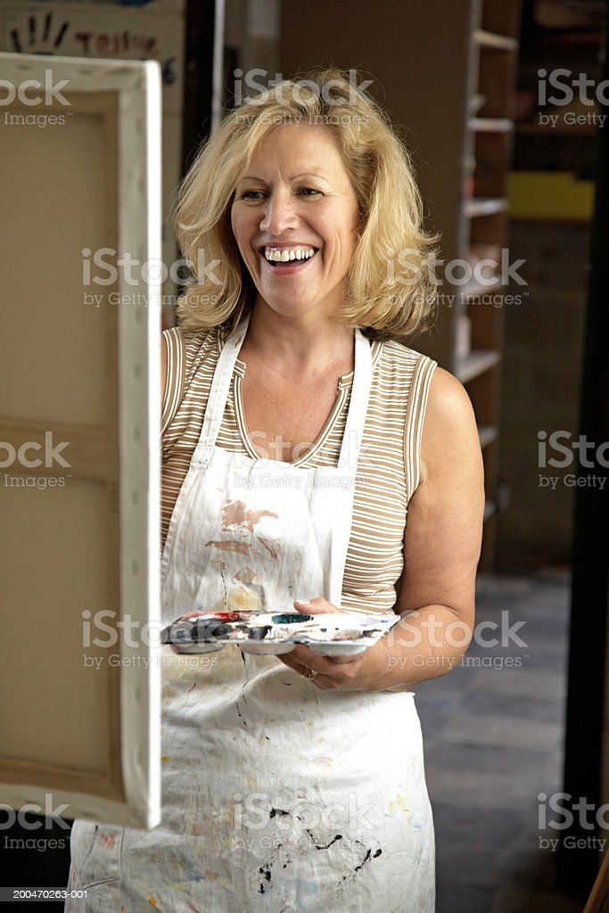 Mature woman painting in classroom, holding palette, smiling royalty-free stock photo