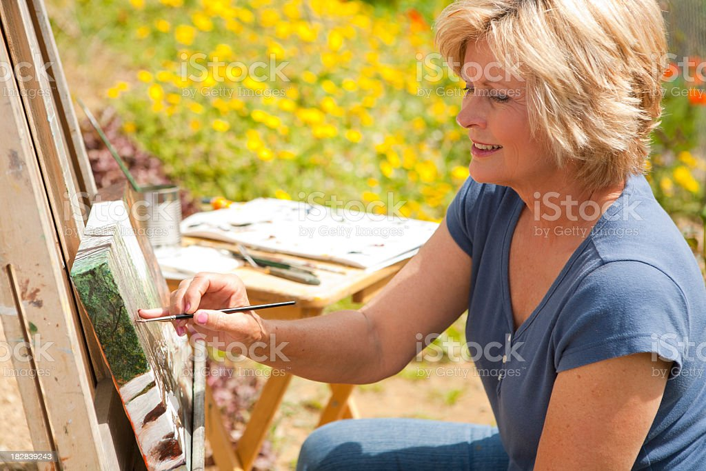 Mature woman painting on a canvas outdoors royalty-free stock photo
