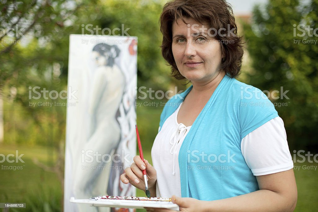 Mature woman painting outdoors. royalty-free stock photo