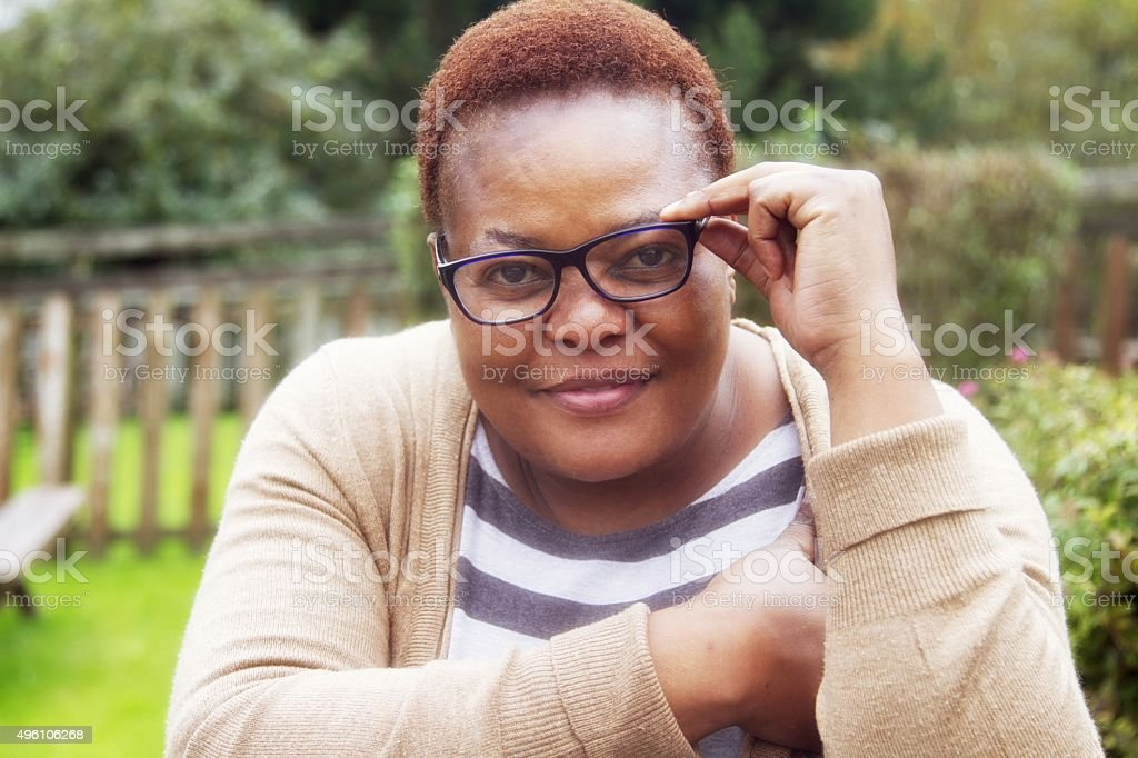mature woman peering over her glasses stock photo