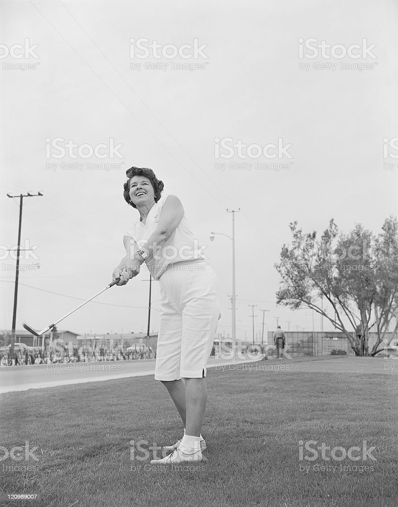 Mature woman playing golf at golf course stock photo