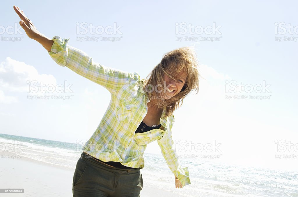 Mature woman playing in the beach stock photo