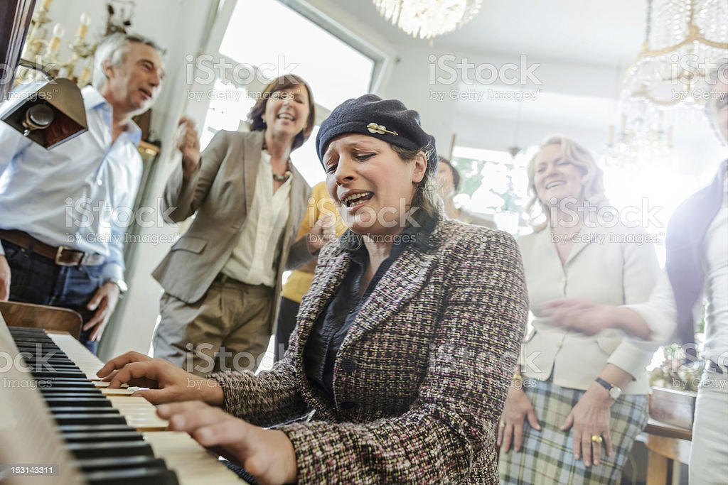 Mature woman playing Piano while friend listen stock photo