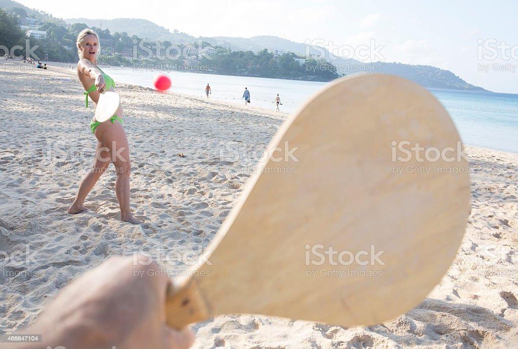 Mature woman plays paddleball, on beach stock photo