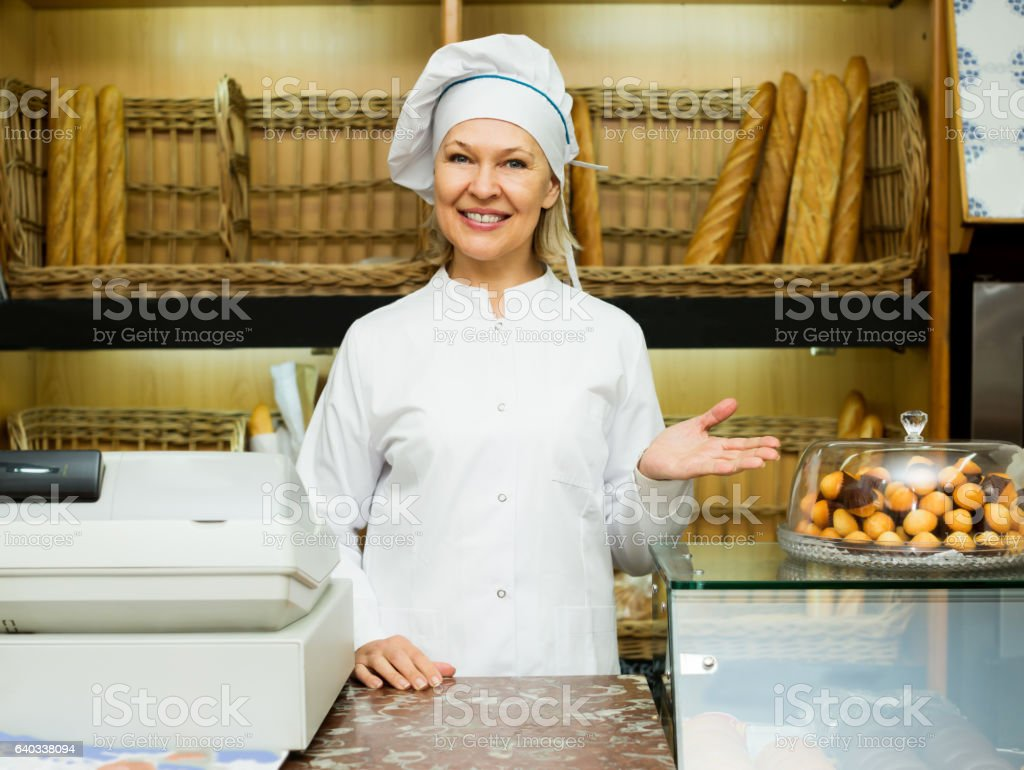 Mature woman posing in bakery with baguettes stock photo
