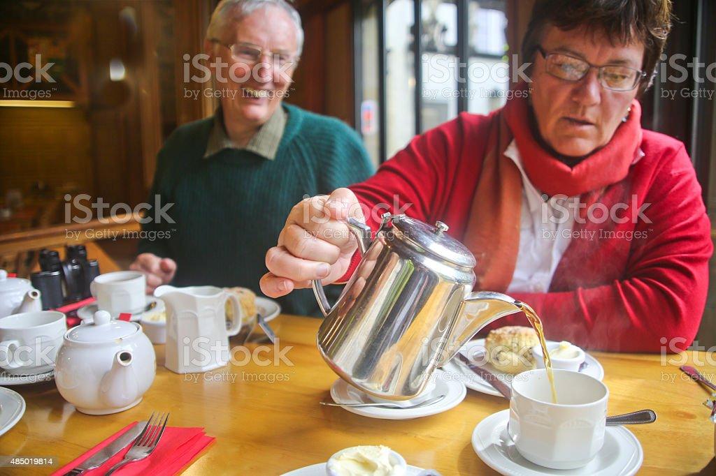 Mature Woman Pouring Tea with her Smiling Husband stock photo