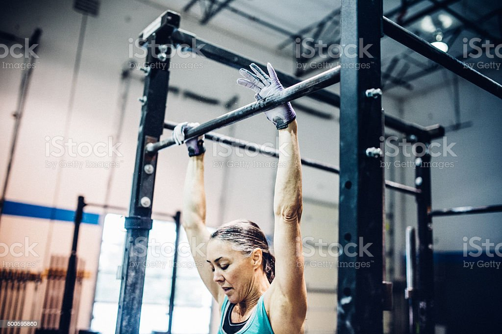 Mature Woman Preparing for Pullups in Gym stock photo