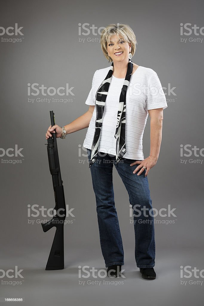 Mature woman proudly stands with her rifle on gray background royalty-free stock photo