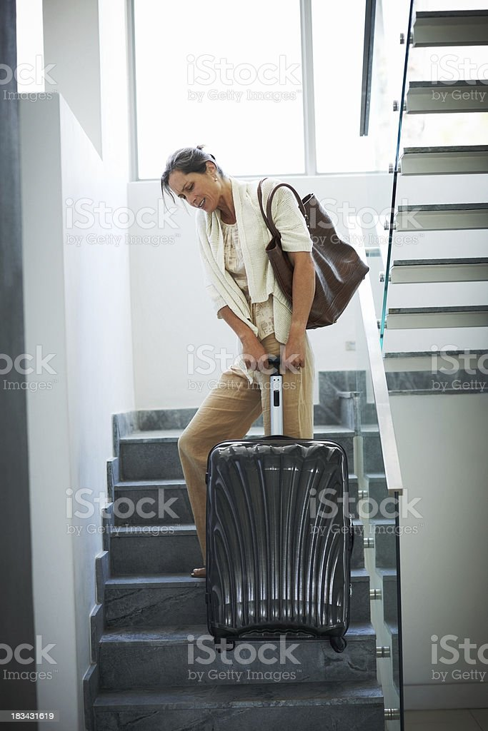Mature woman pulling her heavy luggage up the stairs stock photo