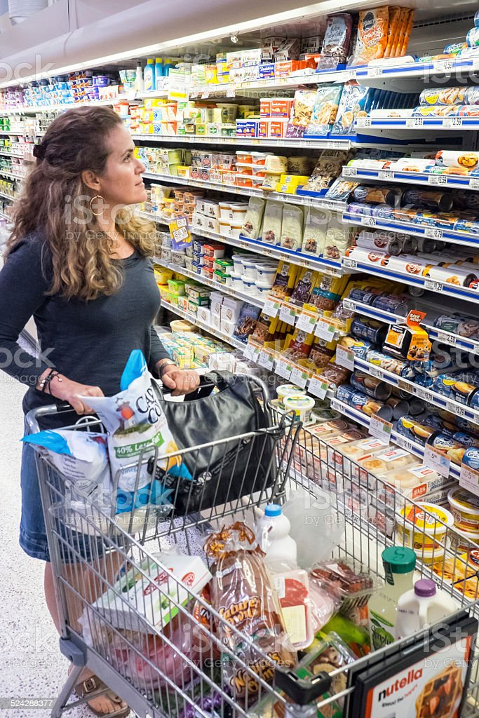Mature woman pushing her shopping cart stock photo