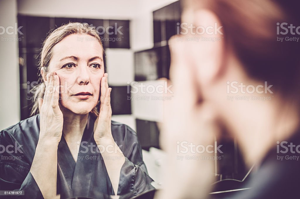 Mature Woman putting cream on her face stock photo