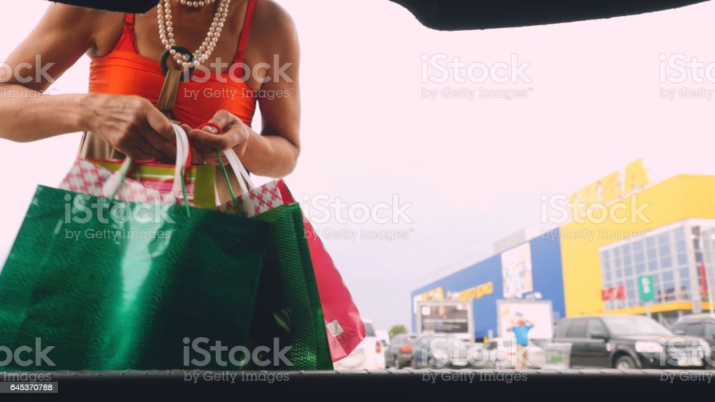 Mature woman putting shopping bags into car trunk at shopping mall outdoor stock photo