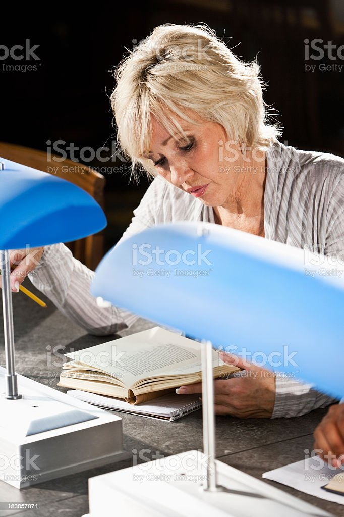 Mature woman reading in library stock photo
