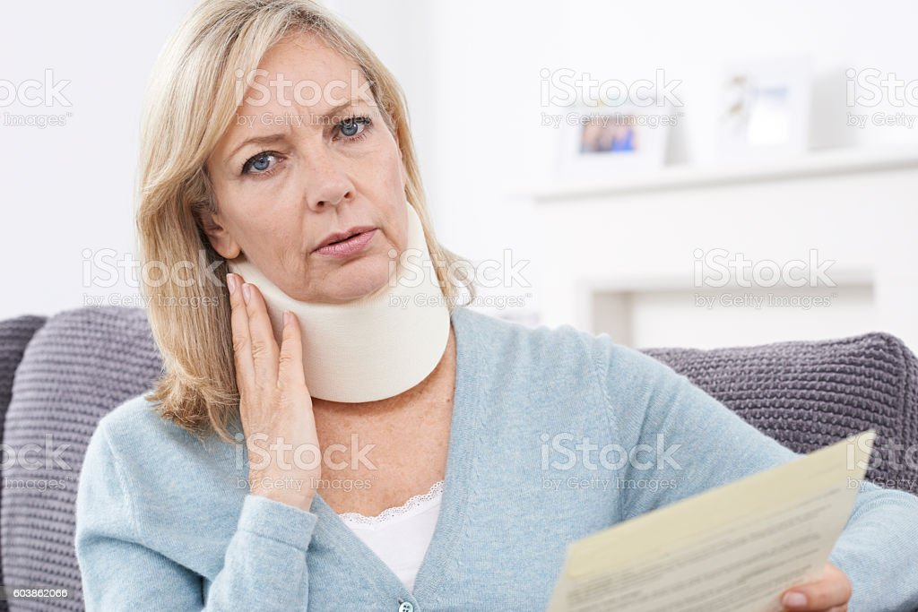 Mature Woman Reading Letter After Receiving Neck Injury stock photo