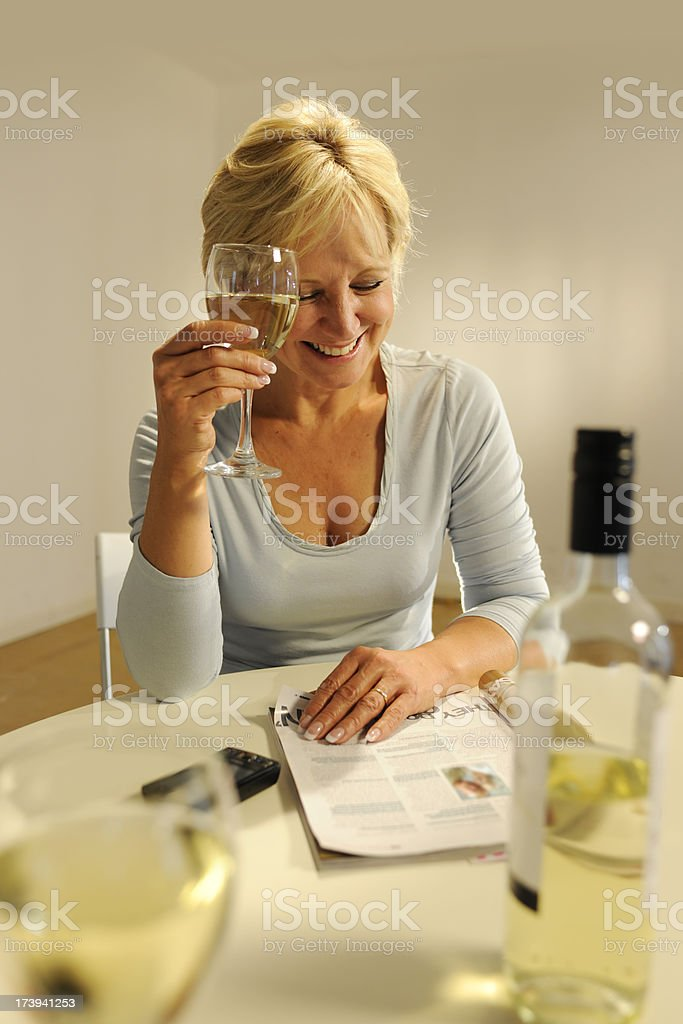 Mature Woman Reading Magazine and Drinking Wine royalty-free stock photo