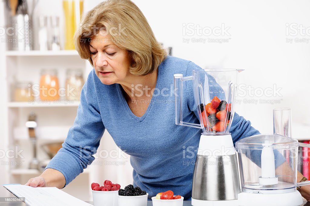 Mature Woman Reading Recipe While Preparing Healthy Drink/ Dessert royalty-free stock photo