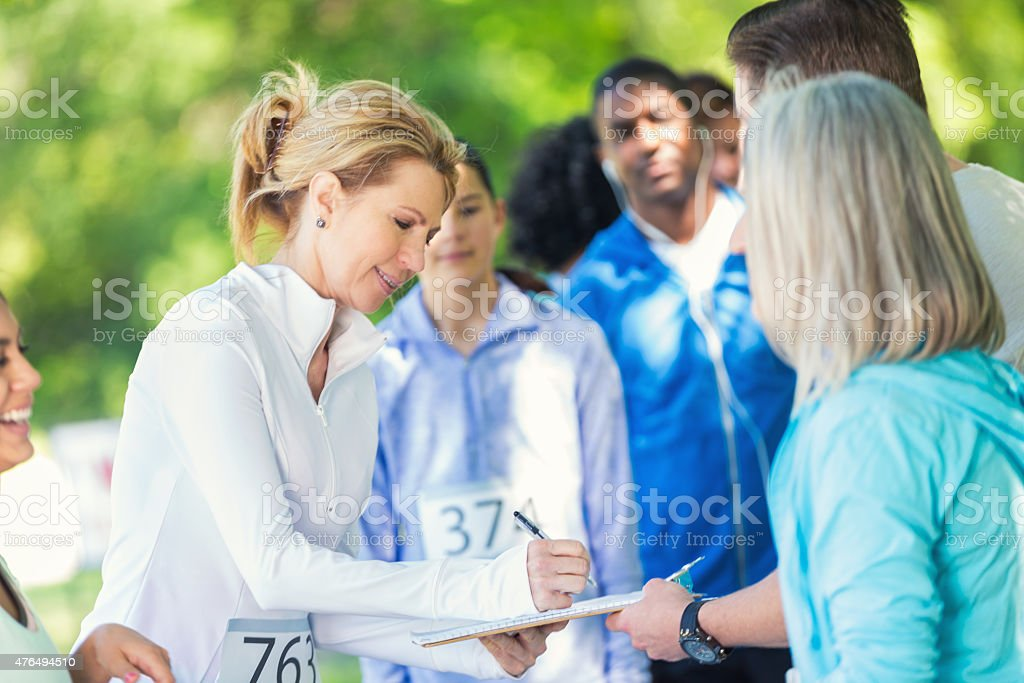 Mature woman registering to compete in marathon or 5k race stock photo